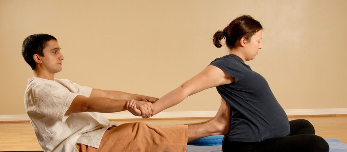 man giving woman client a stretch in massage